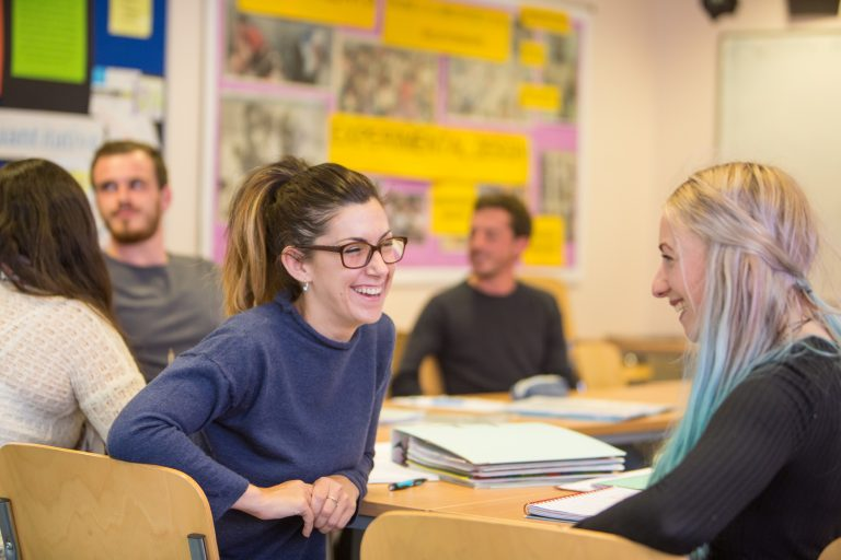 Adult female in classroom laughing