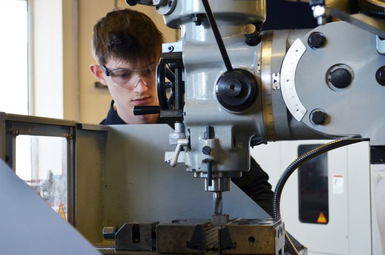 Student wearing safety goggles working at a machine in the Hi Tech & Digital Centre