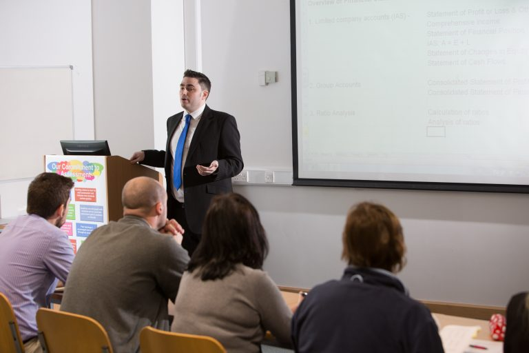Man presenting to a class on a whiteboard.