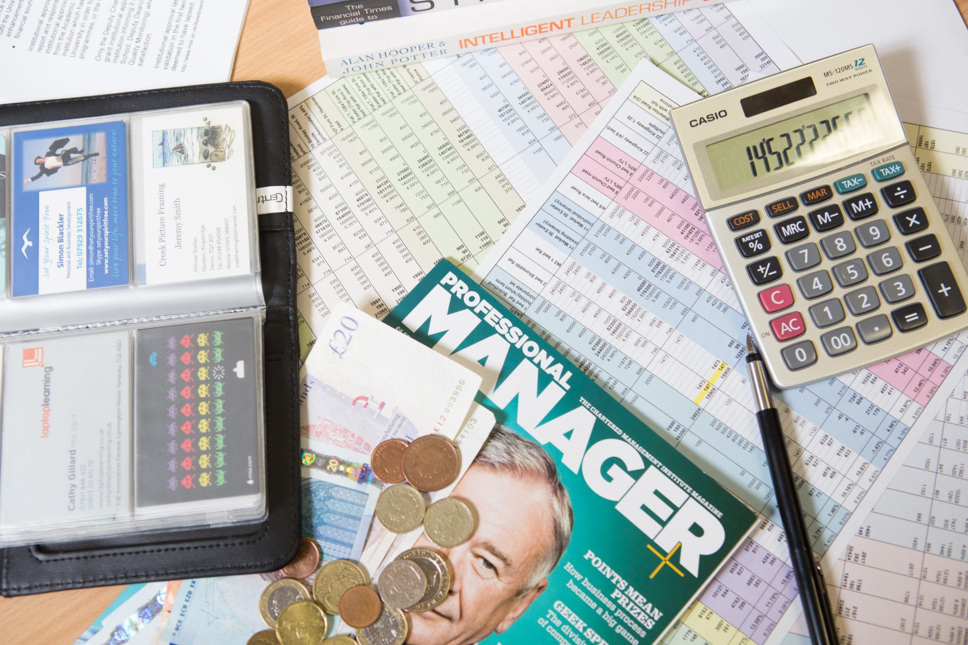 Magazines, forms and a calculator on a desk.