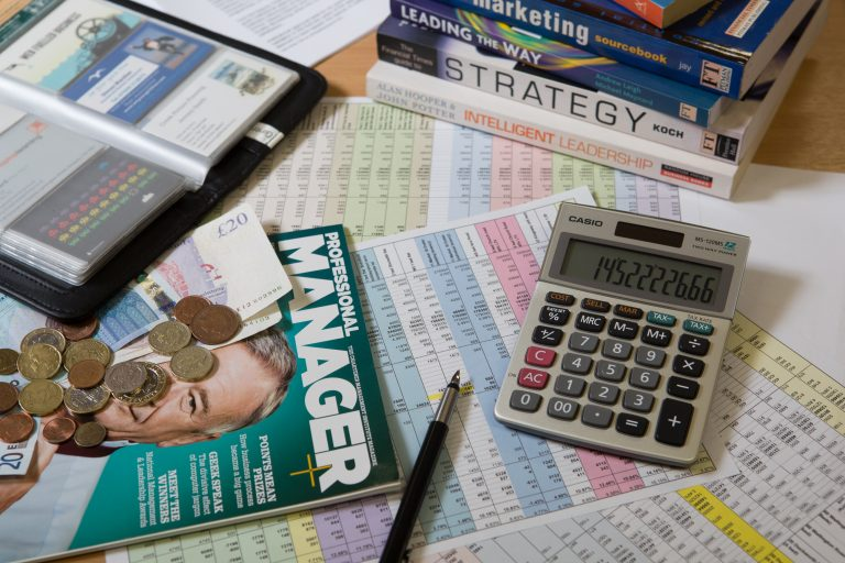 Magazines, forms and calculator on a desk.