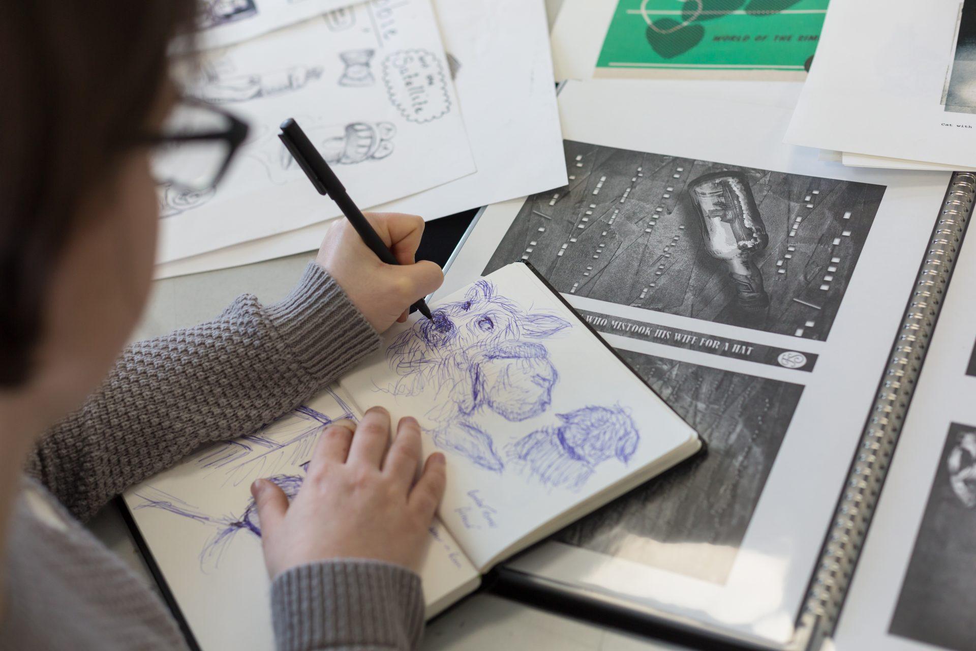 Student drawing in sketchbook.