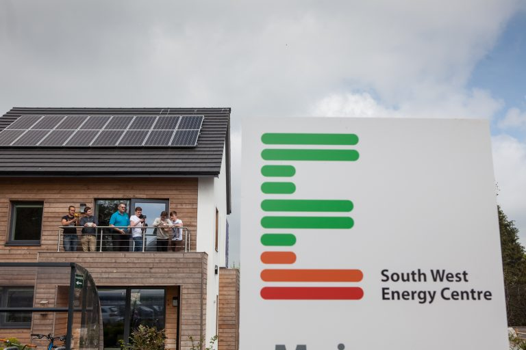 Students in sustainably build house with South West Energy Centre sign