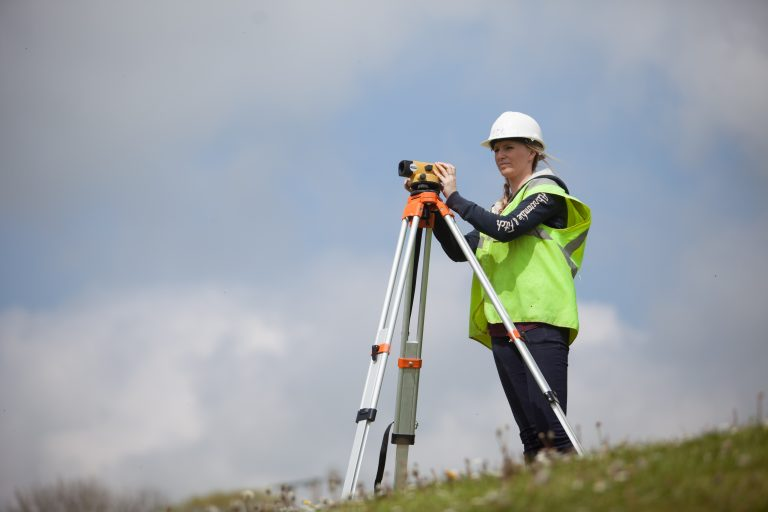 Student in PPE using surveying equipment outside.