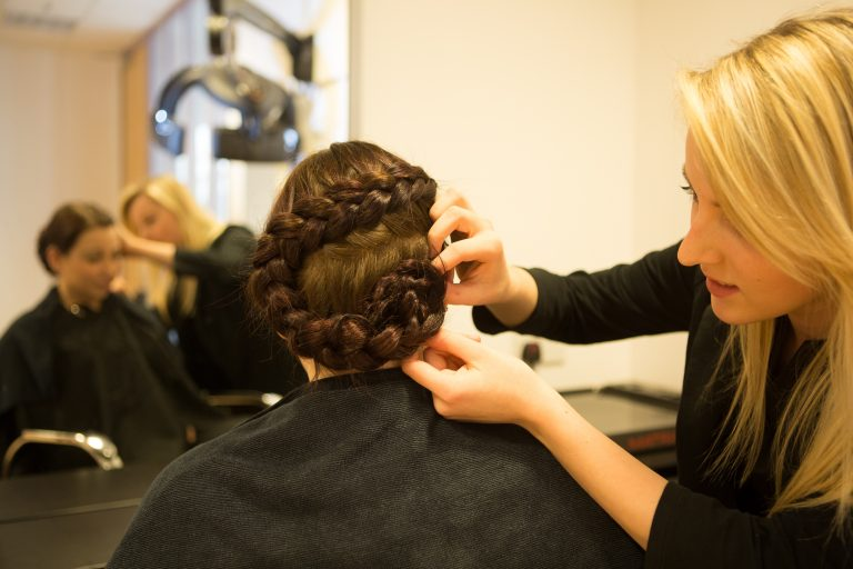 Hairdressing student plaiting a client's hair