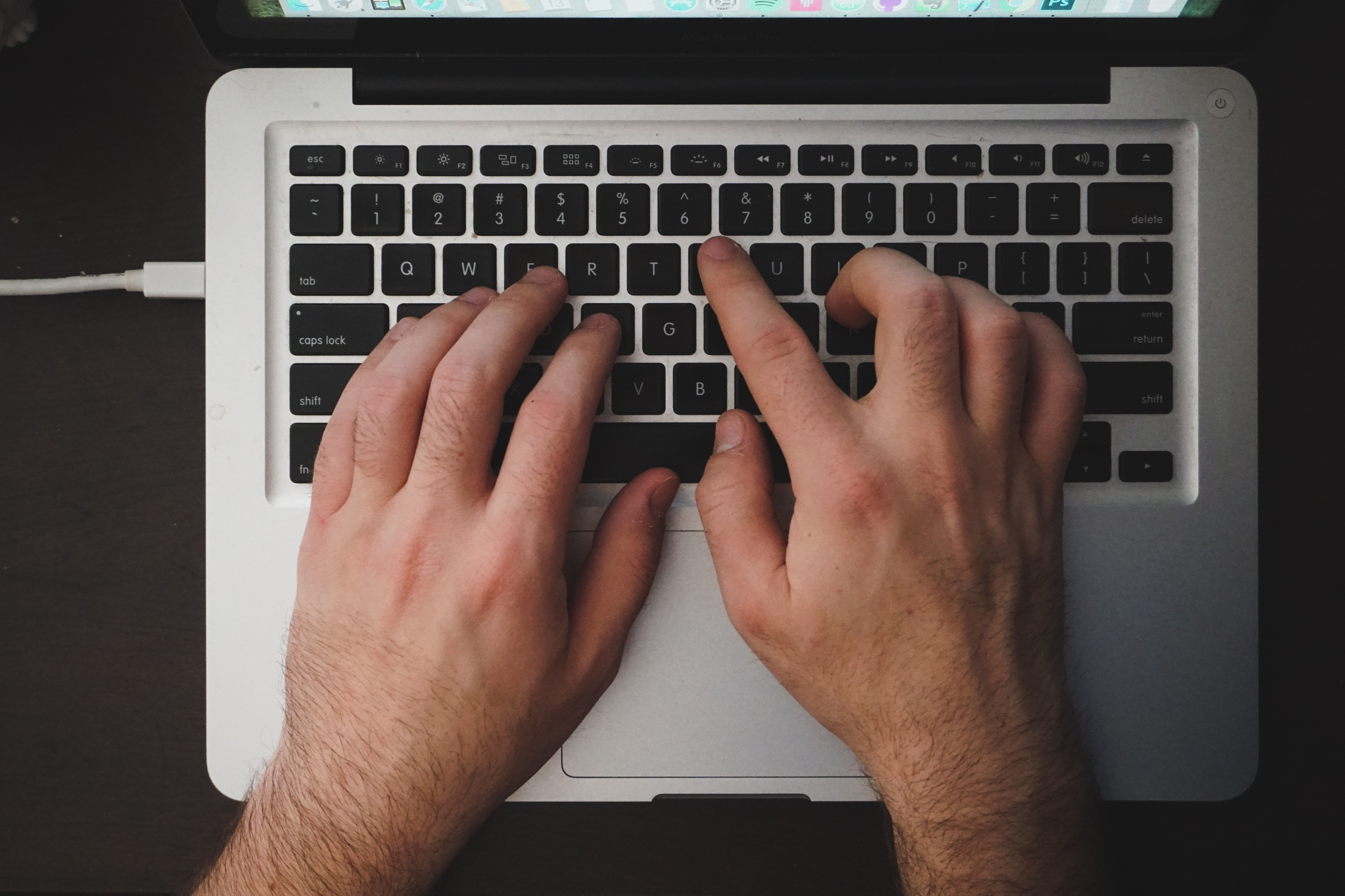 Close up of a man's hands typing on a laptop