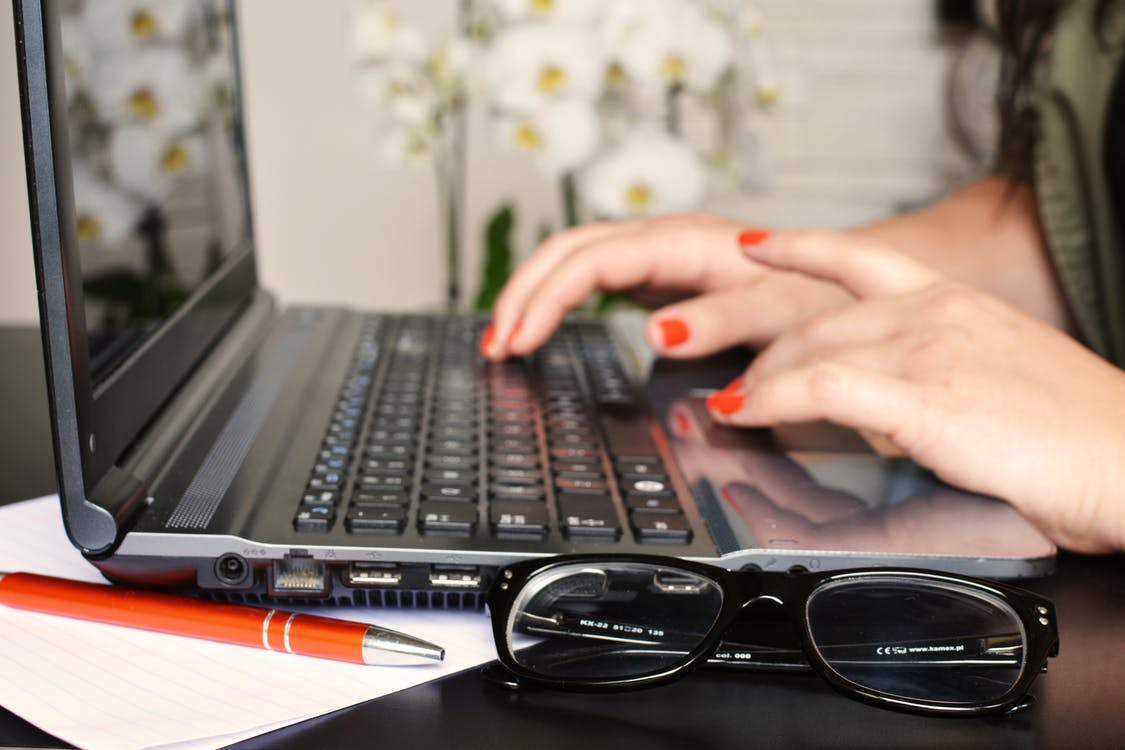 Close up of a woman typing on a laptop