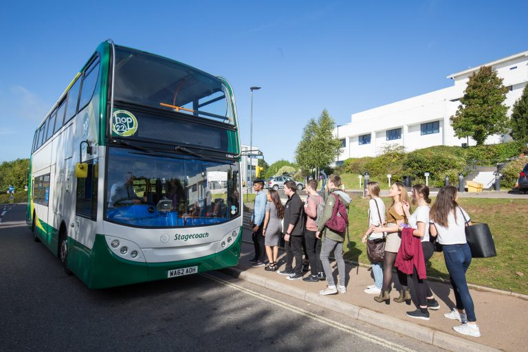 Students queuing for a bus outside College.