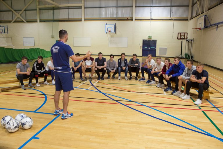Football team listening to their coach sat in Sports Hall.