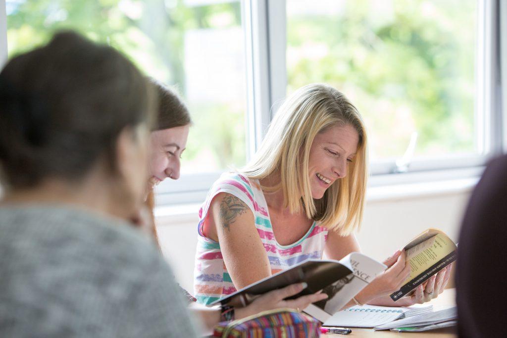 Mature students reading at desks.