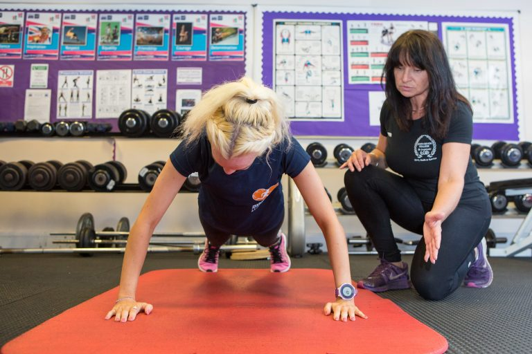 Fitness instructor helping a woman to do press ups