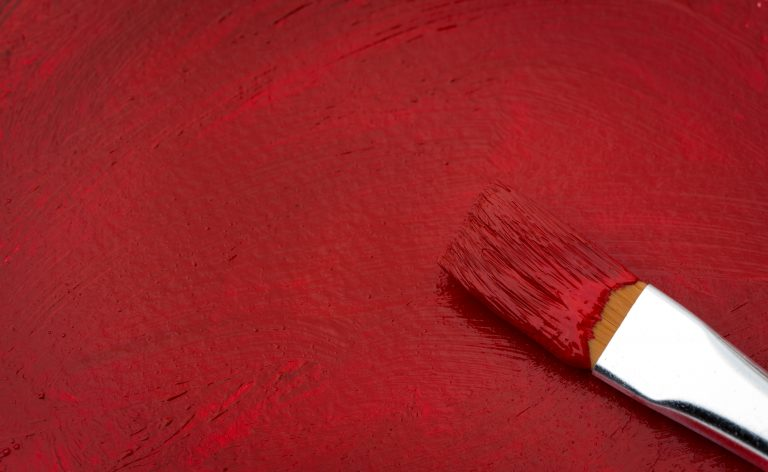Close up of a paintbrush and red paint.