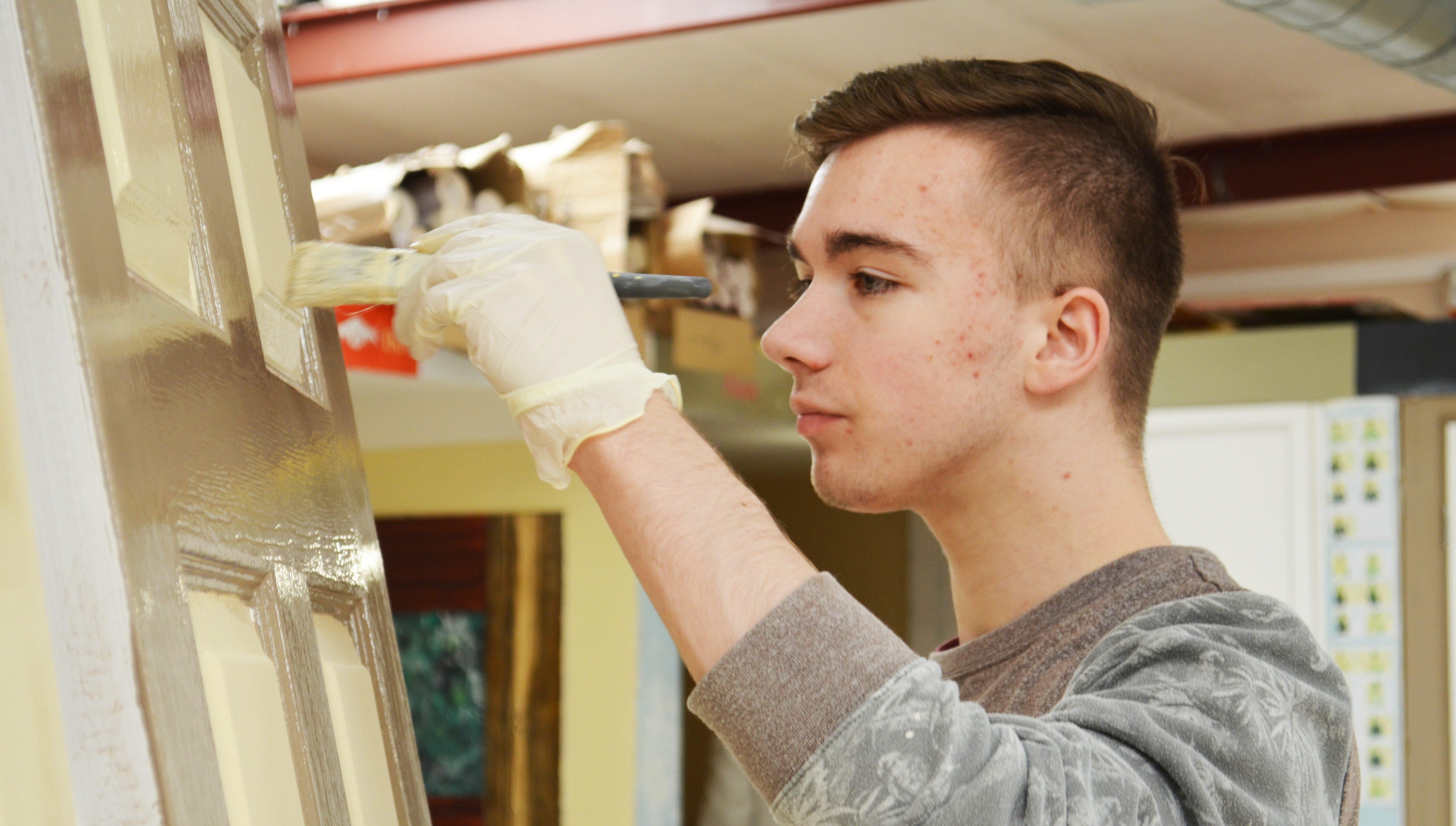 Student painting door.