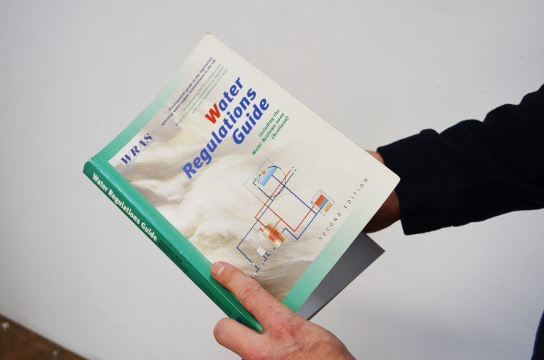 Staff member holding water regulations guide.