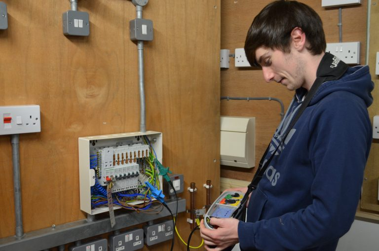 Electrical student testing a circuit in the fuse board.