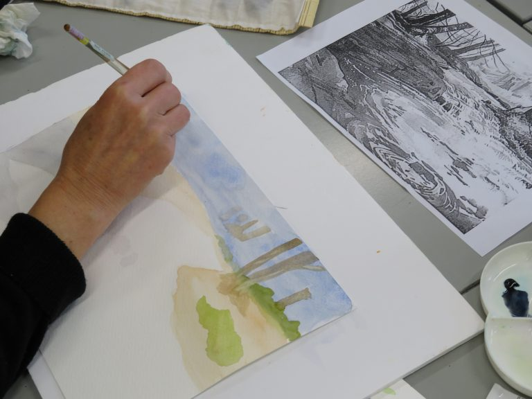Student making a watercolour landscape painting.