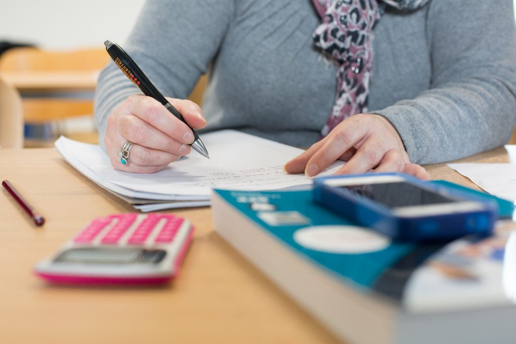 Student writing at a desk with calculator and textbook.