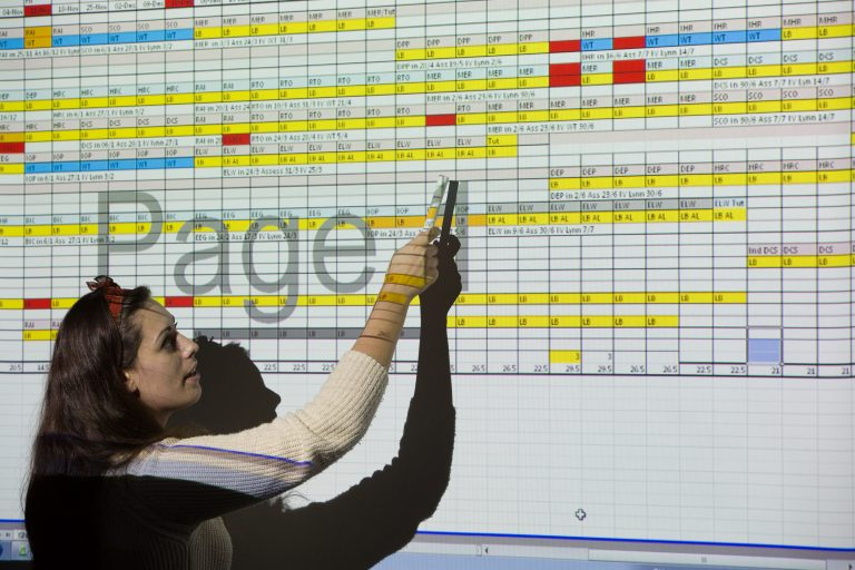 Adult student pointing at a projected spreadsheet.