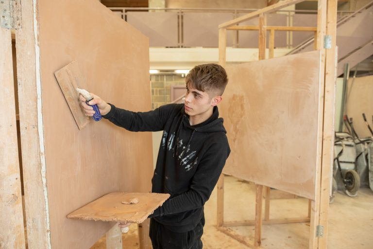 Plastering student practising on wall.
