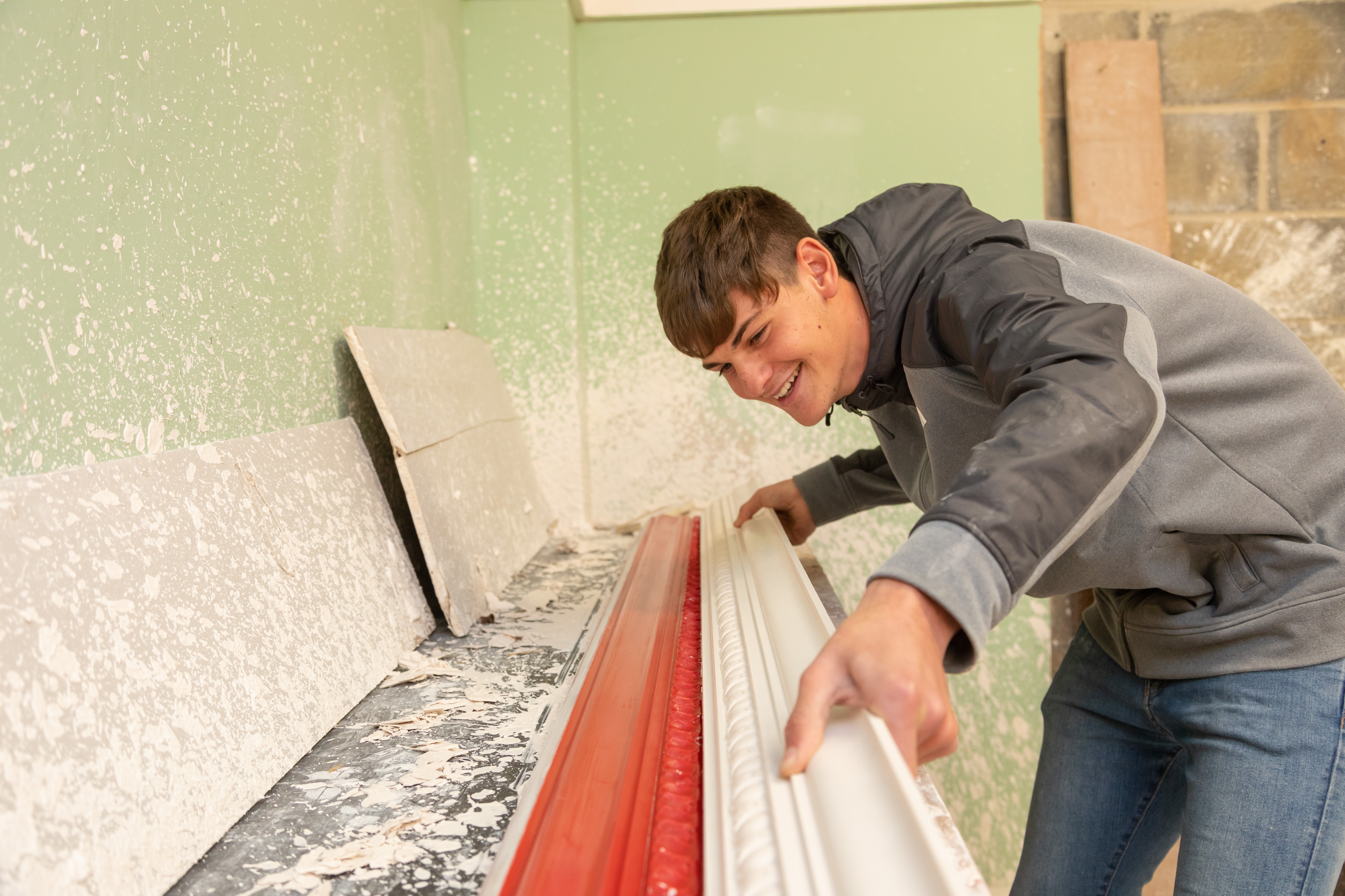 Plastering student creating decorative boarder.