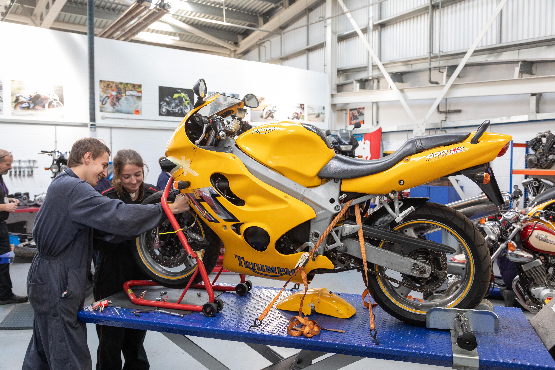 Motorcycle students working on yellow bike.