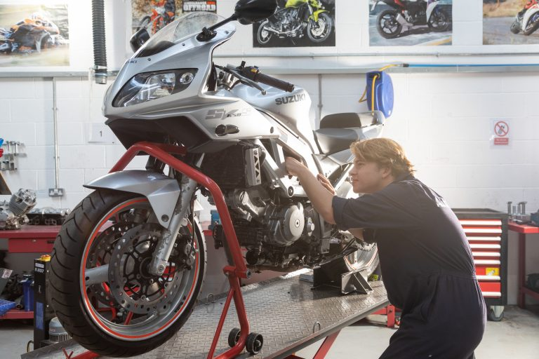 Student working on silver Suzuki Motorcycle