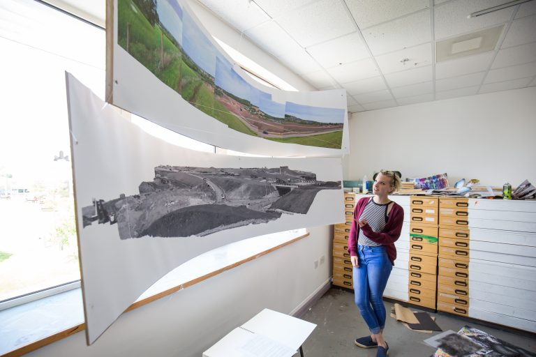 Student looking at a panoramic painting.