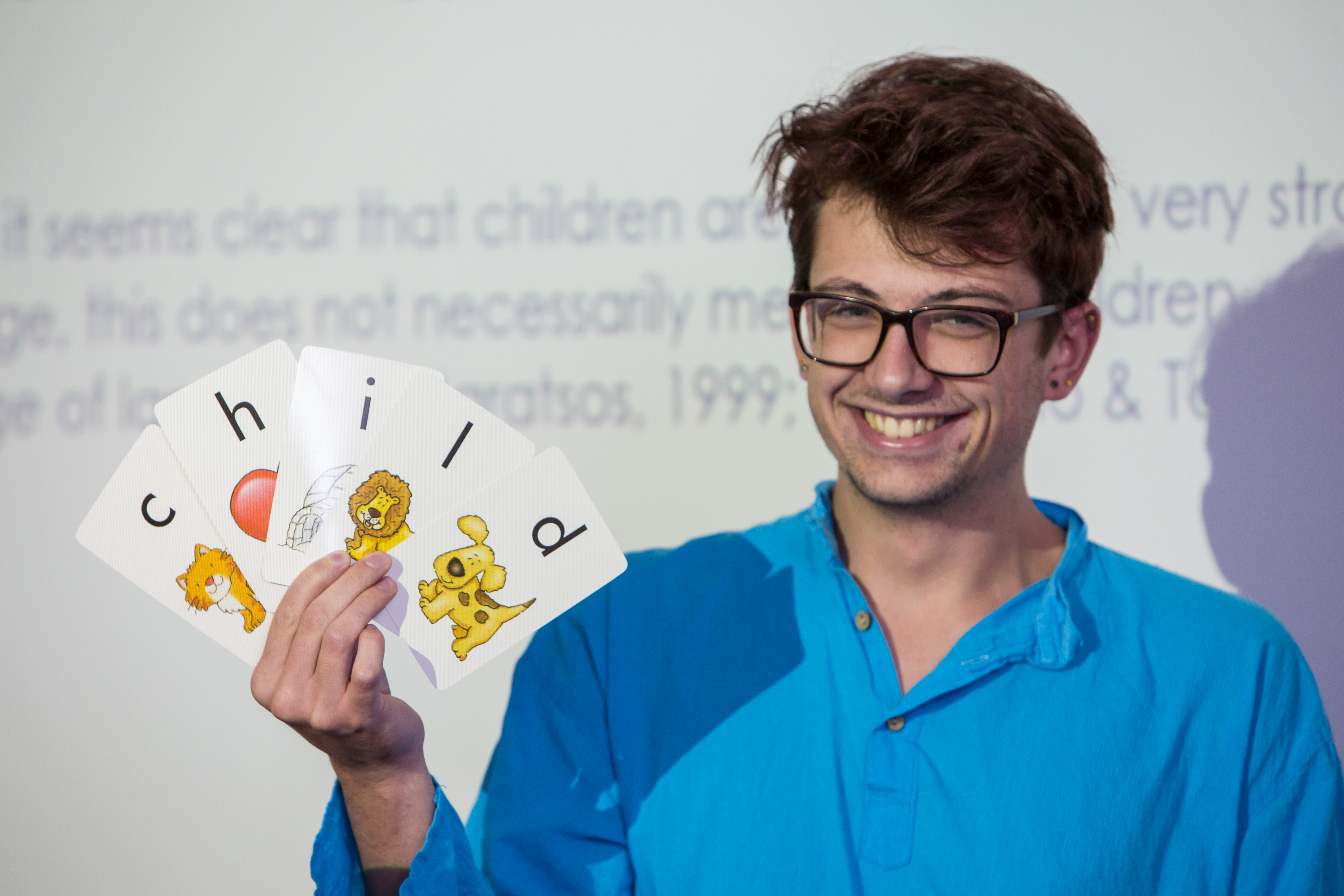 Student holding up playing cards with letters on.