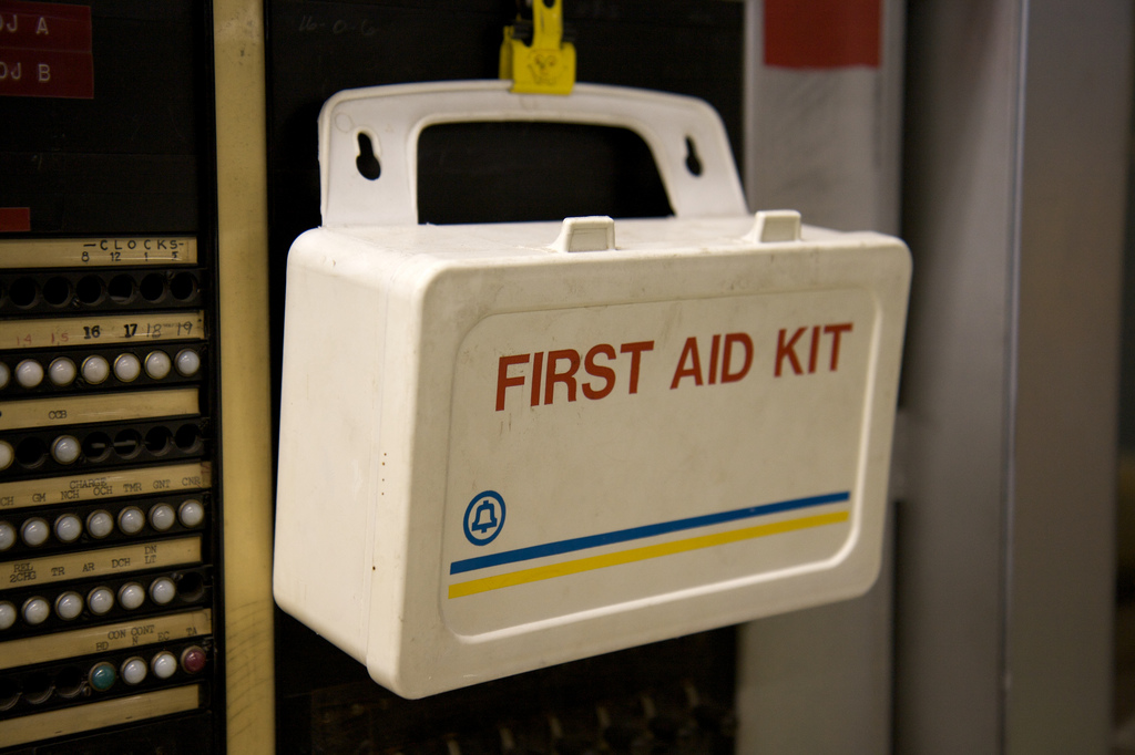 First aid box hanging up on a wall.