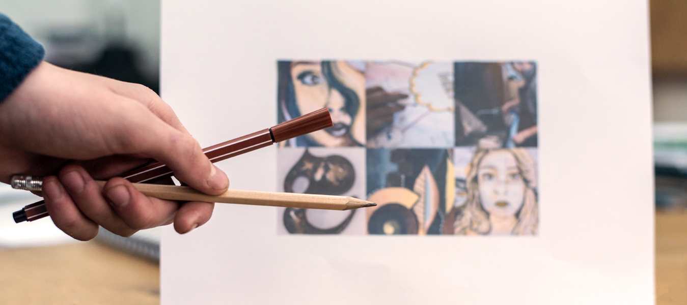 Pen and pencil being held in front of a picture.