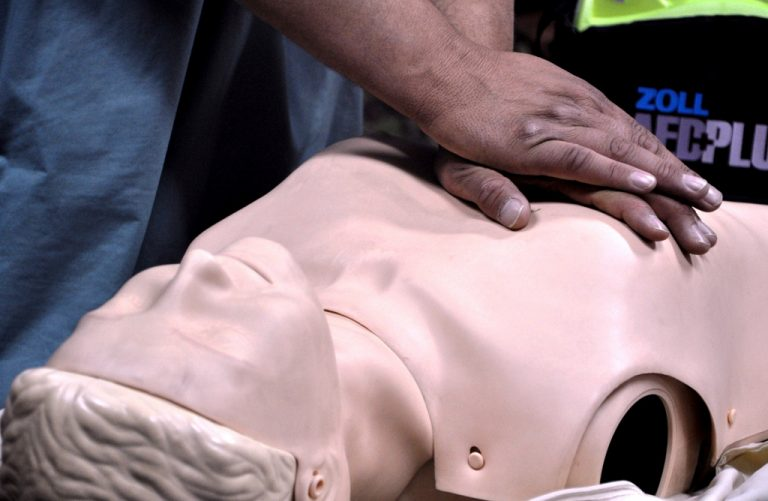 Man practising CPR on manikin.
