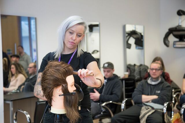 Barbering lecturer showing students a demonstration.
