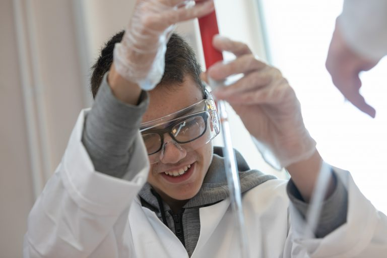 Male student holding pipette.