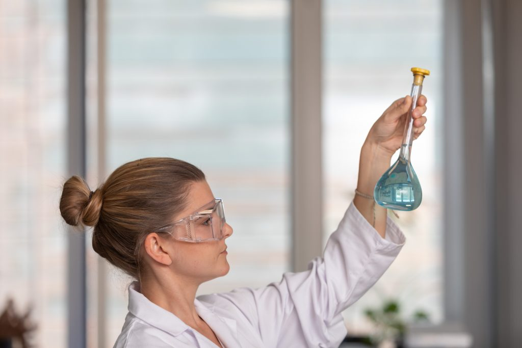 Student holding glass flask at eye level.