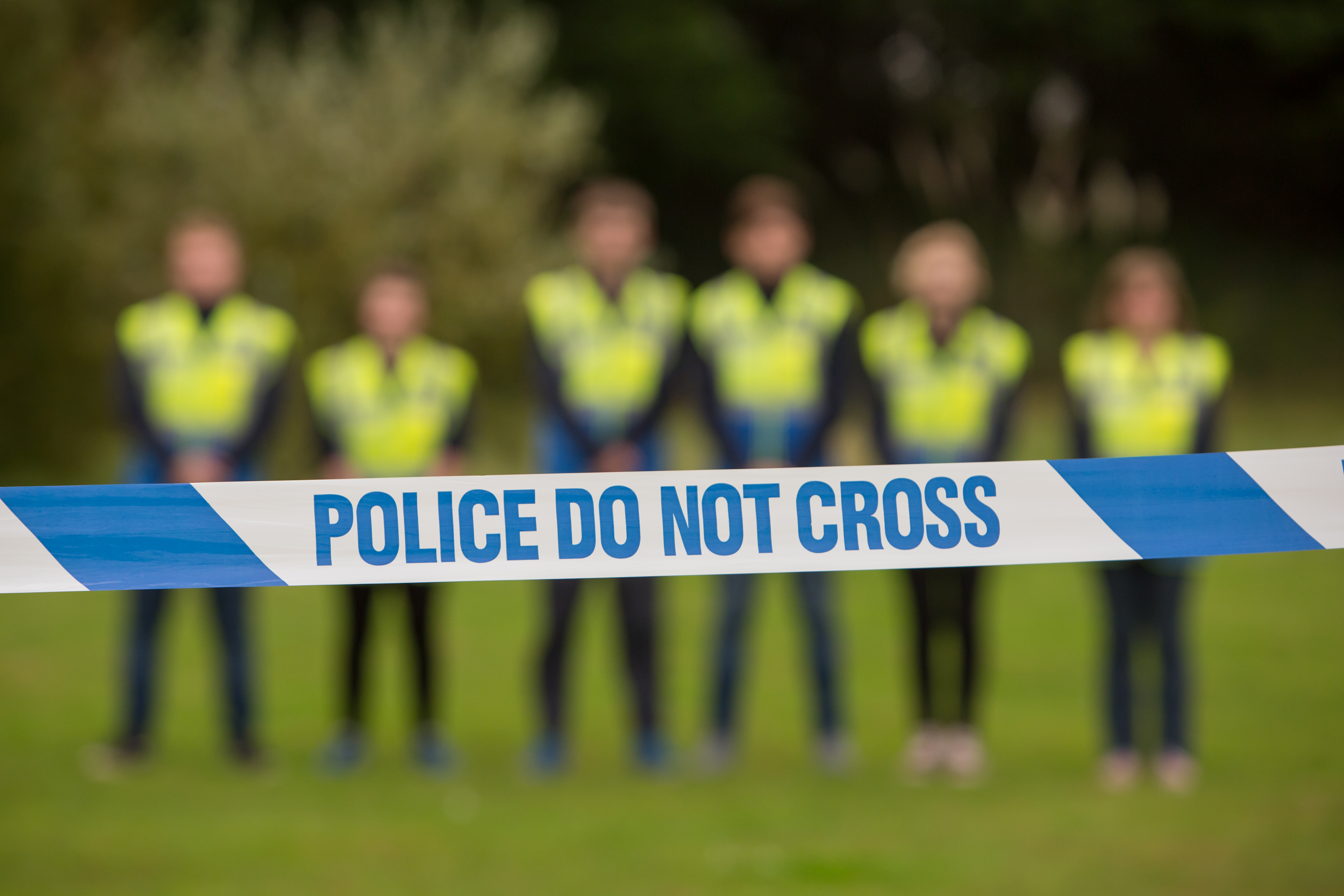 Public services students stood in front of 'police do not cross' tape.