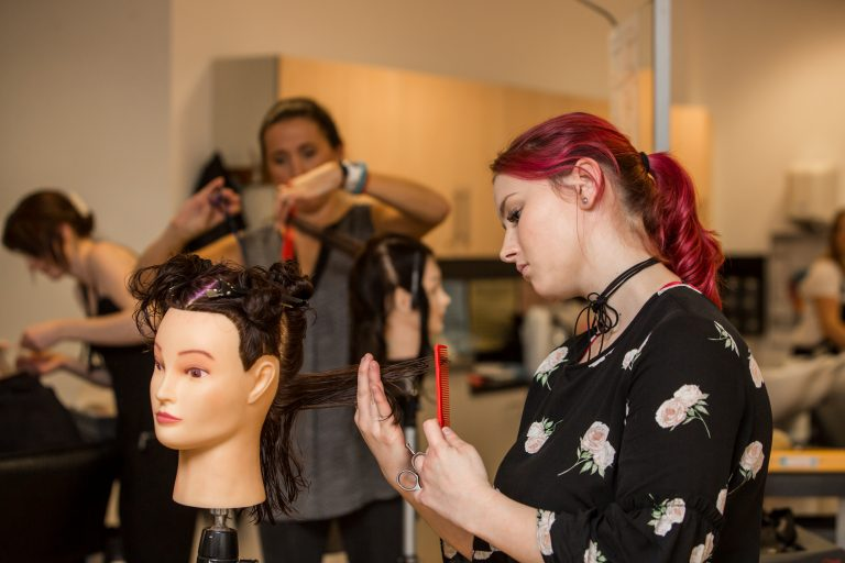 Hairdressing student cutting hair.