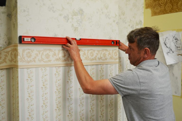 Adult painting and decorating student checking straight edge on wallpaper border.