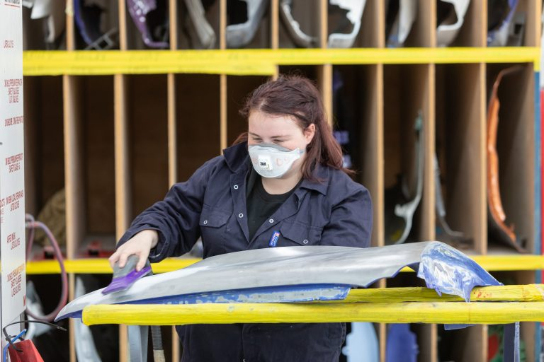 Vehicle body repair student working on her project.