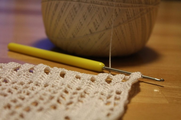 Close up of crochet needle and material.