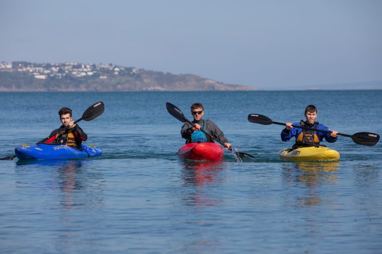 Three students kayaking.