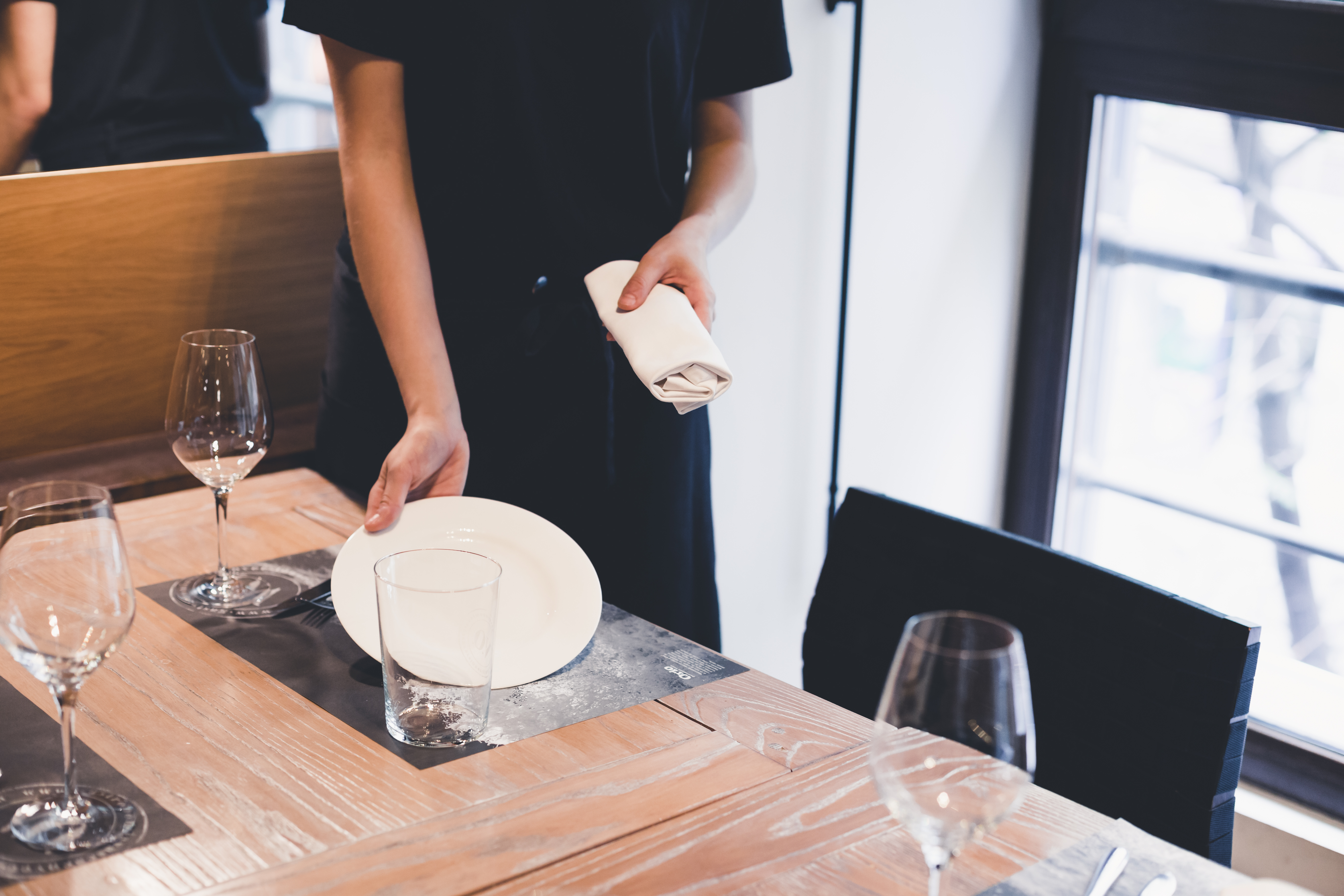 Waitress placing plate on table.