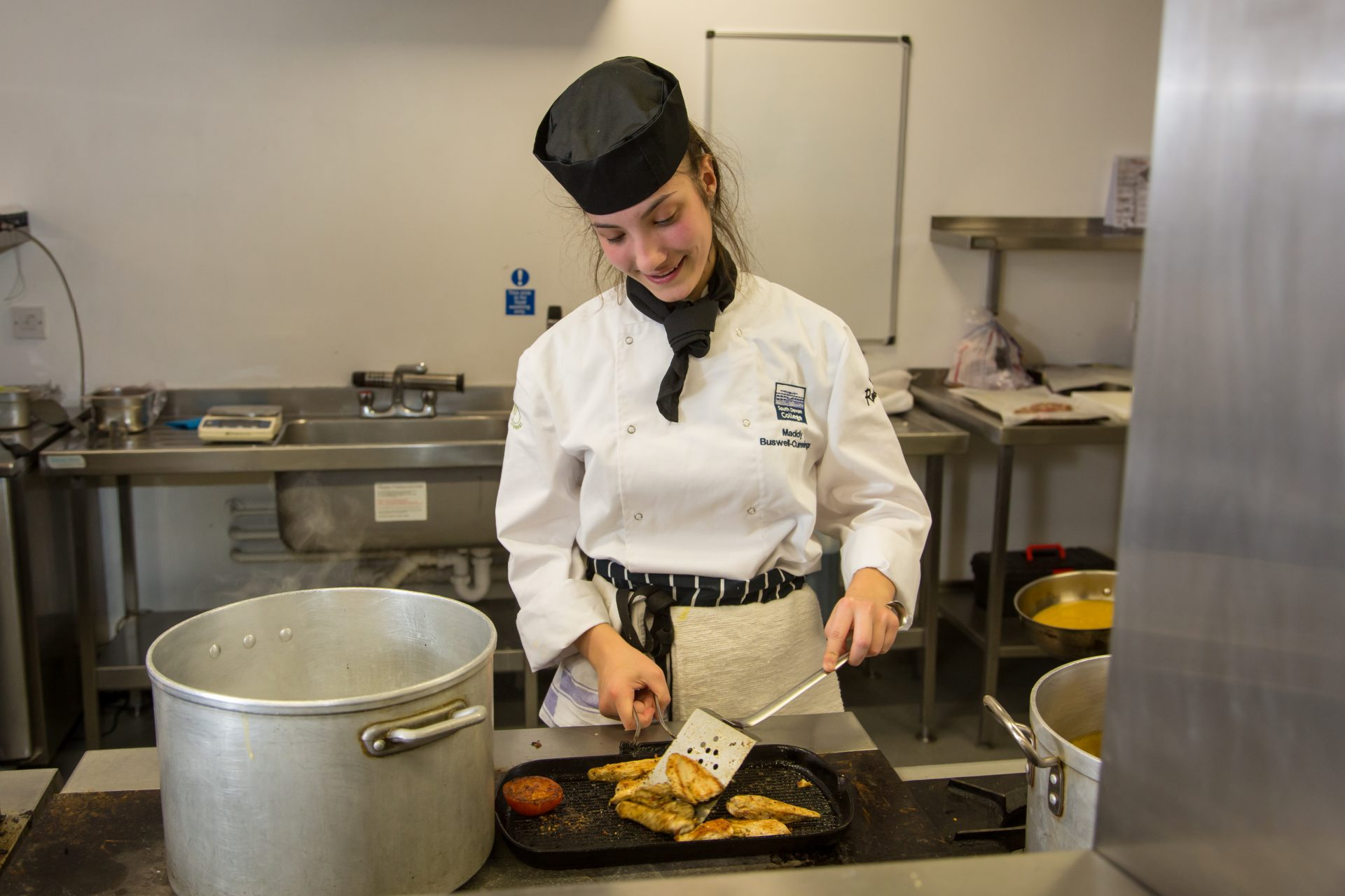Production chef apprentice in the kitchen cooking.