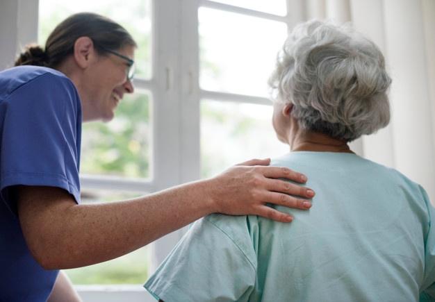 Nurse in blue scrubs taking care of elderly lady next to a window