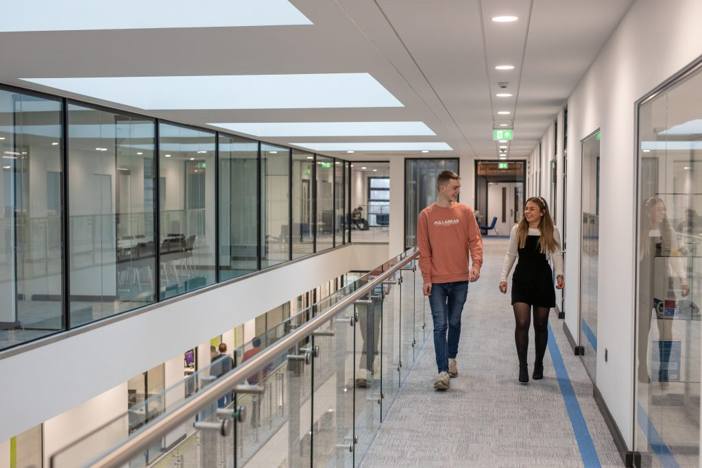 Two students walking along the corridor in the Hi Tech & Digital Centre